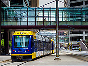 03 MAY 2017 - MINNEAPOLIS, MN: A Minneapolis light rail train goes under the skyway on 5th Street in Minneapolis. The skyways are enclosed pedestrian overpasses that connect downtown buildings. The Minneapolis Skyway was started in the early 1960s as a response to covered shopping malls in the suburbs that were drawing shoppers out of the downtown area. The system grew sporadically until 1974, when the construction of the IDS Center and its center atrium, called the Crystal Court, served as a hub for the downtown skyway system. There are 8 miles of skyways, connecting most of the downtown buildings from Target Field (home of the Minnesota Twins) to US Bank Stadium (home of the Minnesota Vikings). In the last five years many upscale downtown apartment buildings and condominium developments have been added to the system, allowing downtown residents to live and work downtown without going outside.    PHOTO BY JACK KURTZ