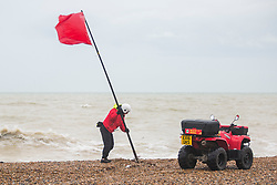 © Licensed to London News Pictures. 31/12/2017. Brighton, UK. A lifeguard places red flags and warning signs as powerful waves are hitting Brighton and Hove seafront. Photo credit: Hugo Michiels/LNP
