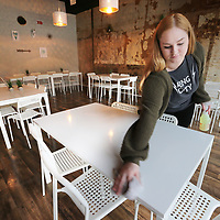 Amaris Franks cleans off tables in the newly completed meeting rooms at Crave downtown Tupelo Thursday.