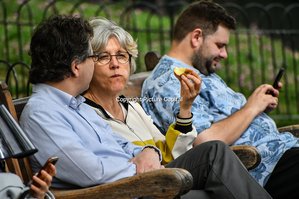 Tourists eating apple at St James park and a lovely weather on 23 April 2019, London, UK.