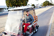 Robert Johnson rides in his golf cart while his dogs Jewel and Buster, both rescues, walk with him in Sun City, Arizona January 8, 2010. Robert has lived in Sun City for 14 years. He and his wife Jessie moved to Sun City from Minnesota because they wanted to live somewhere where there is something going on when the sun goes down. His wife is very involved and does yoga, acrylic painting, water colors and more.