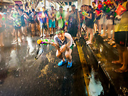 13 APRIL 2018 - BANGKOK, THAILAND:  A man gets squirted by a mob in a water fight on Silom Road during the first day of Songkran in Bangkok. Songkran is the traditional Thai New Year celebration best known for water fights.     PHOTO BY JACK KURTZ