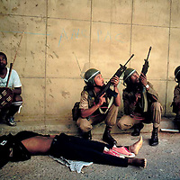 POLITICS CONFLICT SOUTH AFRICA MAR 1994: A member of the Inkatha Freedom party lies dead near the African National Congress headquarters 'Shell House' March 1994, Johannesburg, South Africa.  His shoes are taken off for the journey to the next life. There was extensive violence and thousands of deaths in the run-up to the first non-racial elections in South Africa in April 1994. (Photo by Greg Marinovich / Getty Images)