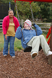 Woman with learning disability at swing with carer