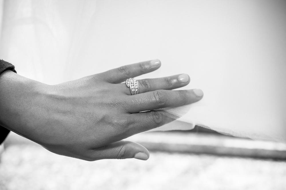 A bride runs her hand along the hem of her wedding dress in Brattleboro, VT.