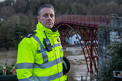 © Licensed to London News Pictures. 26/02/2020. Ironbridge, UK. Chief Superintendent Tom Harding, Head of Local Policing for West Mercia Police,  stands in front of The Iron Bridge in Ironbridge, he ordered the evacuation of part of the town when flood barriers moved approximately three feet under the strain of the rising water levels on the River Severn. Photo credit: Peter Manning/LNP
