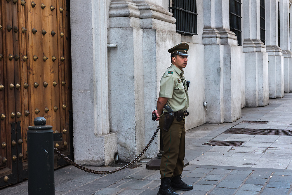 Santiago, Chile--April 6, 2018. A police officer is standing guard outside a door to the presidential palace in Santiago, Chile.  Editorial use only.