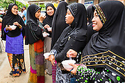 07 JULY 2013 - NARATHIWAT, NARATHIWAT, THAILAND:   Thai Muslim women eat frozen snacks provided by Royal Thai Marines in Narathiwat Sunday. Royal Thai Marines in Narathiwat province held a special ceremony Sunday in advance of Ramadan. They presented widows, orphans and indigent people with extra rice and food as a part of the Thai government's outreach to resolve the Muslim insurgency that has wracked southern Thailand since 2004. The Holy Month of Ramadan starts on about July 9 this year. Muslims are expected to fast from dawn to dusk, engage in extra prayers, recitation of the Quran and perform extra acts of charity during Ramadan. It is the holiest month of the year for Muslims.  PHOTO BY JACK KURTZ