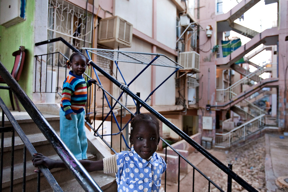 "Sudanese refugee girls plays in the cage staircase of the sinsin building  on February 28 2011 in Eilat. The municipality hung 1,500 red flags around the city as a sign of warning and put up hundreds of banners reading: ""Protecting our home, the residents of Eilat are drawing the line on infiltration."" Eilat Mayor Meir Yitzhak Halevi said that 10 percent of the city's population was currently made up of migrants and that the residents feel that the city has been conquered...Photo by Olivier Fitoussi."