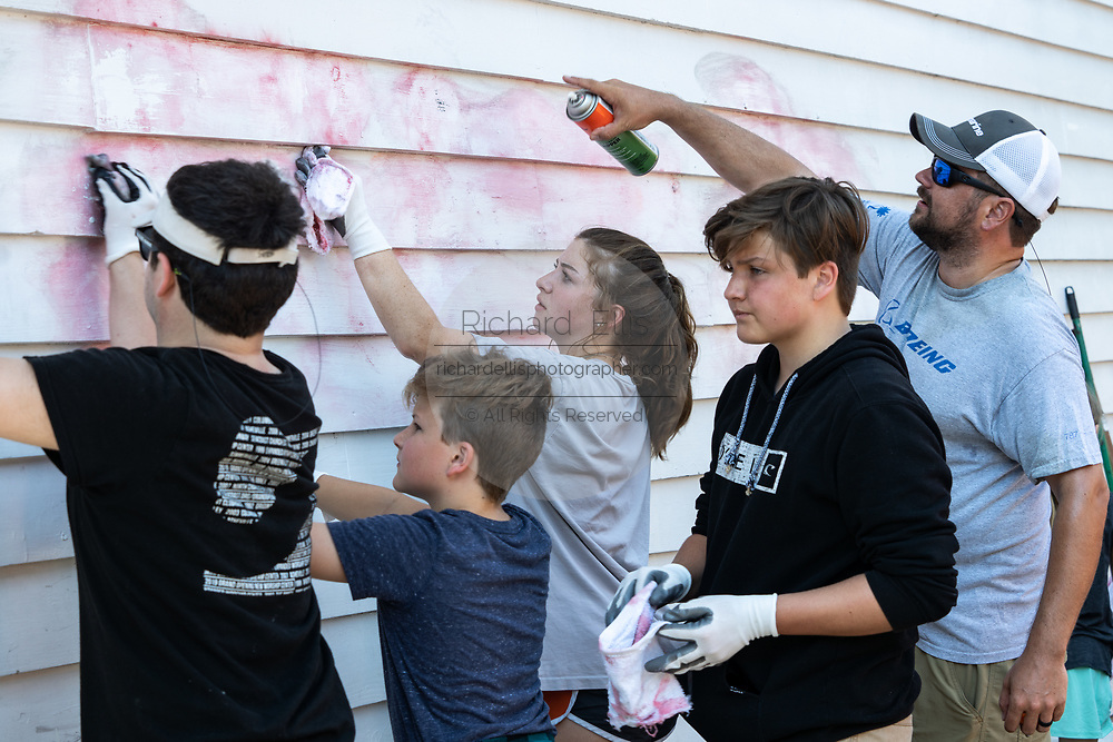 Charleston, United States. 31 May, 2020. Volunteers help clean graffiti off a shop wall along the King Street shopping district after a protest over the death of George Floyd, turned violent and destructive May 31, 2020 in Charleston, South Carolina. Floyd was choked to death by police in Minneapolis resulting in protests sweeping across the nation.  Credit: Richard Ellis/Alamy Live News