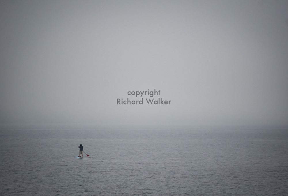 2013 October 24 - A person on a stand up paddleboard in heavy fog on Puget Sound off Charles Richey Sr. Viewpoint, Seattle, WA. By Richard Walker