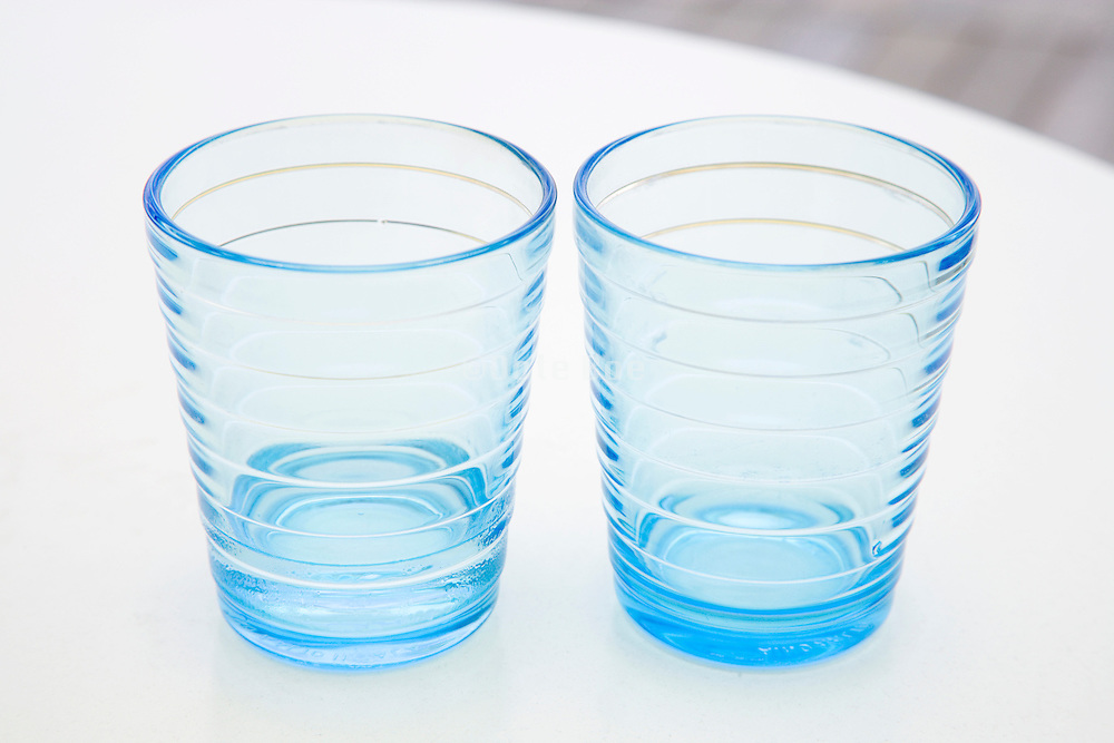 two empty blue water glasses on a white table