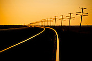 Endless line of telephone poles along rail road tracks at sunrise Imperial Valley, CA.