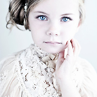 Young girl with blonde hair and blue eyes wearing white lace dress with hand to face