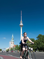 cyclist on street with Fernsehturm or Television Tower to rear in Alexanderplatz in Mitte Berlin Germany
