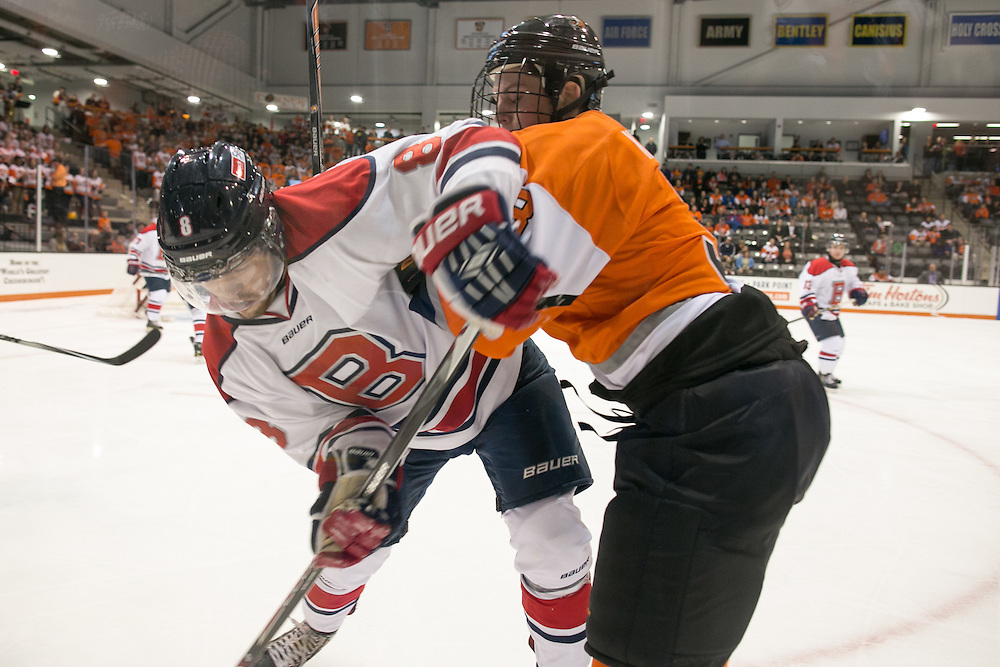 RIT Junior Captain Alexander Kuqali hits Brock University's Spencer Turcotte during a game at the Gene Polisseni Center on Saturday, October 4, 2014.