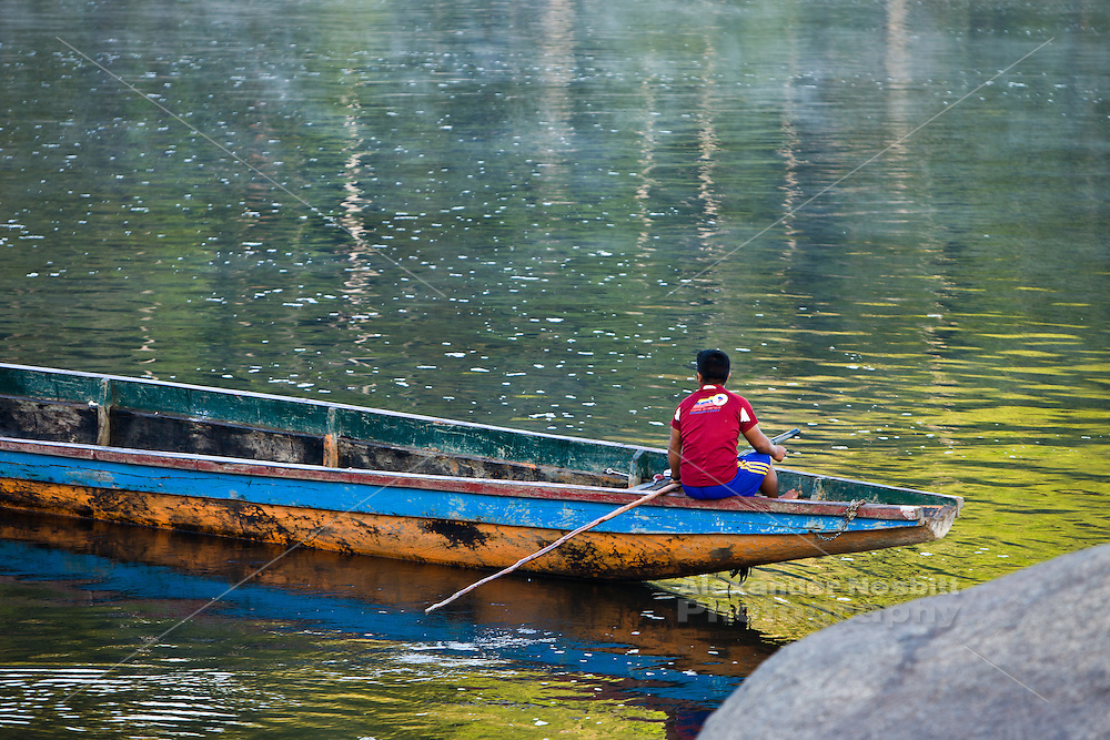 Boat driver in dugout canoe on the Rio Caura, Venezuela