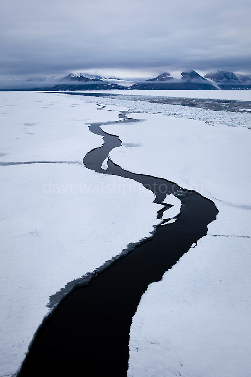 A pathway opens in the landfast sea ice, forming a question mark in Dijmhna Sund, Nioghalvfjerdsfjorden, in Greenland's remote northeast corner. The Arctic Ocean sea ice continues to decline; as more white ice, which reflects sunlight back into space, is lost to due the burning of fossil fuels, the remaining dark water absorbs heat, creating a feedback effect spells bad news for the Arctic, and the global climate. Greenland, 2009<br />