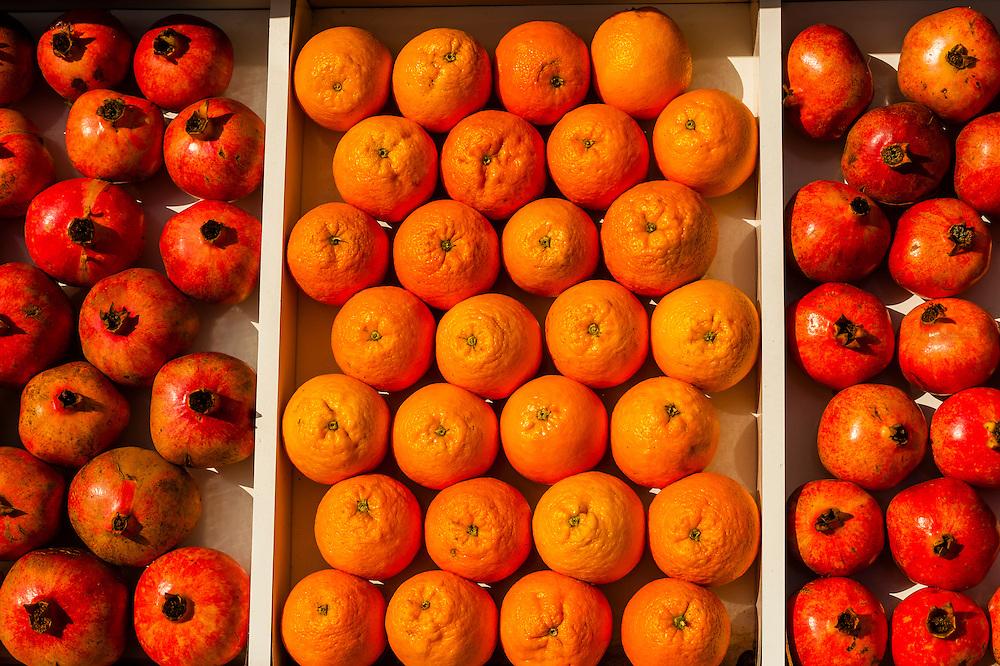 Pomegranate and oranges for sale at a sidewalk market, Eilat, Israel.