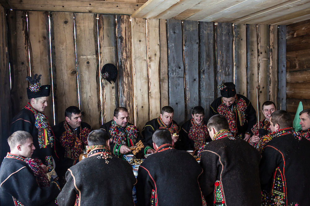 ILTSI, UKRAINE - JANUARY 7: Men wearing traditional Hutsul clothing eat and drink snacks and vodka offered by a local family after singing for them in celebration of Orthodox Christmas on January 7, 2015 in Iltsi, Ukraine. The men gather in groups and travel house to house for twelve days singing songs until they've visited every home in the village. (Photo by Brendan Hoffman/Getty Images) *** Local Caption ***
