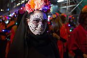 New York, NY - October 31, 2015. A smiling Calavera Catarina marching with the Mexican torusist office with a coronet of red, orange, and pink flowers.