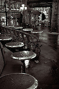 cafe table in the rain,night shot,with newstand lit in background,black and white verticle
