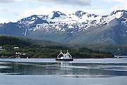 Small ship in sea near Ornes, Nordland, Norway snow capped rugged mountains