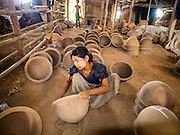 02 NOVEMBER 2014 - TWANTE, YANGON DIVISION, MYANMAR: A workers polishes the inside of clay pots in a pottery factory in Twante, Myanmar. Twante, about 20 miles from Yangon, is best known for its traditional pottery. The pottery makers are struggling to keep workers in their sheds though. As Myanmar opens up to outside investments and its economy expands, young people are moving to Yangon to take jobs in the better paying tourist industry or in the factories that are springing up around Yangon.    PHOTO BY JACK KURTZ