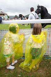 © Licensed to London News Pictures. 21/07/2015. Llanelwedd, UK. Children put on rain capes as they watch horses in the Main Ring. The Royal Welsh Show is hailed as the largest & most prestigious event of it's kind in Europe. In excess of 200,000 visitors are expected this week over the four day show period - 2014 saw 237,694 visitors, 1,033 tradestands & a record 7,959 livestock exhibitors. The first ever show was at Aberystwyth in 1904 and attracted 442 livestock entries. Photo credit: Graham M. Lawrence/LNP
