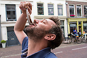 In Utrecht eet een man een Hollandse Nieuwe met uitjes op straat.<br />