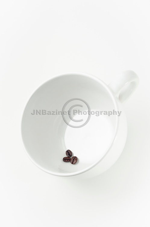 Small cluster of coffee beans in white ceramic cup