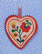 A heart cushion with flower design hanging from a pushpin.