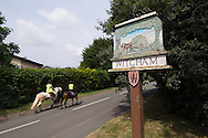 Photo by Andrew Tobin/Tobinators Ltd - 07710 761829 - Two horses pass the sign for the village of Witcham during the World Peashooting Championships held at Witcham, Cambridgeshire, UK on 13th July 2013. Run in conjunction with the village fair, the Championships have been held in Witcham since 1971 when they were started by a Mr Tyson, the village schoolmaster, in order to raise funds for the village hall.Competitors come from as far afield as the USA and New Zealand to attempt to win the event. The latest technology is often used, including laser sights and titanium and carbon fibre peashooters. All peashooters must conform to strict length rules, not exceeding 12 inches, and have to hit a target 12 feet away. Shooting 5 peas at a plasticine target attached to a hay bale, the highest scorers move through the initial rounds to a knockout competition, followed by a sudden death 10-pea shootout.