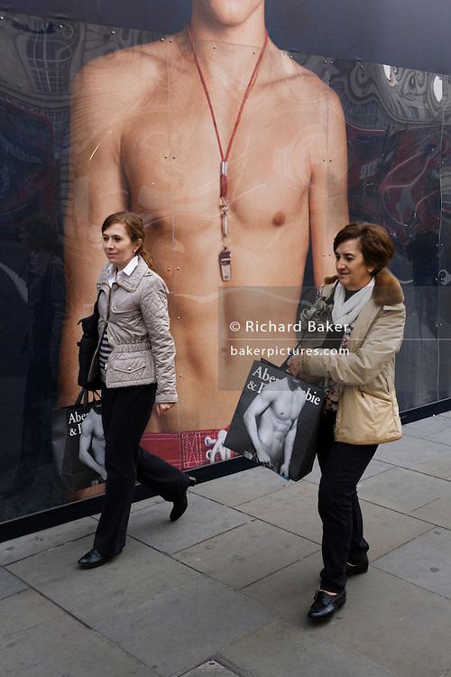 Women walk past a giant ad mural of a bare-chested young male model, carrying Abercrombie shopping bags.