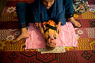 Ghair Bibi's daughter wraps her two-month-old baby in a towel. <br /> Ghair Bibi assisted the delivery herself at their home without any complications. Karachi, Pakistan, 2011