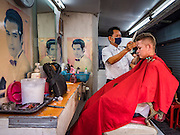 "06 FEBRUARY 2017 - BANGKOK, THAILAND: A barber cuts a customer's hair in a small barbershop in what used to be known as Kalabok Market under the Phra Khanong Bridge in the Phra Khanong district of Bangkok. Kalabok is the Thai word for hairdresser and the market was called Kalabok because there were many barbershops and hairdressers under the bridge. In 1985, the city changed the name of the market to ""Singha Market."" There are still about 10 small men's barbershops, most with just one barber, and four women's salons, most with one hairdresser,  under the bridge.      PHOTO BY JACK KURTZ"