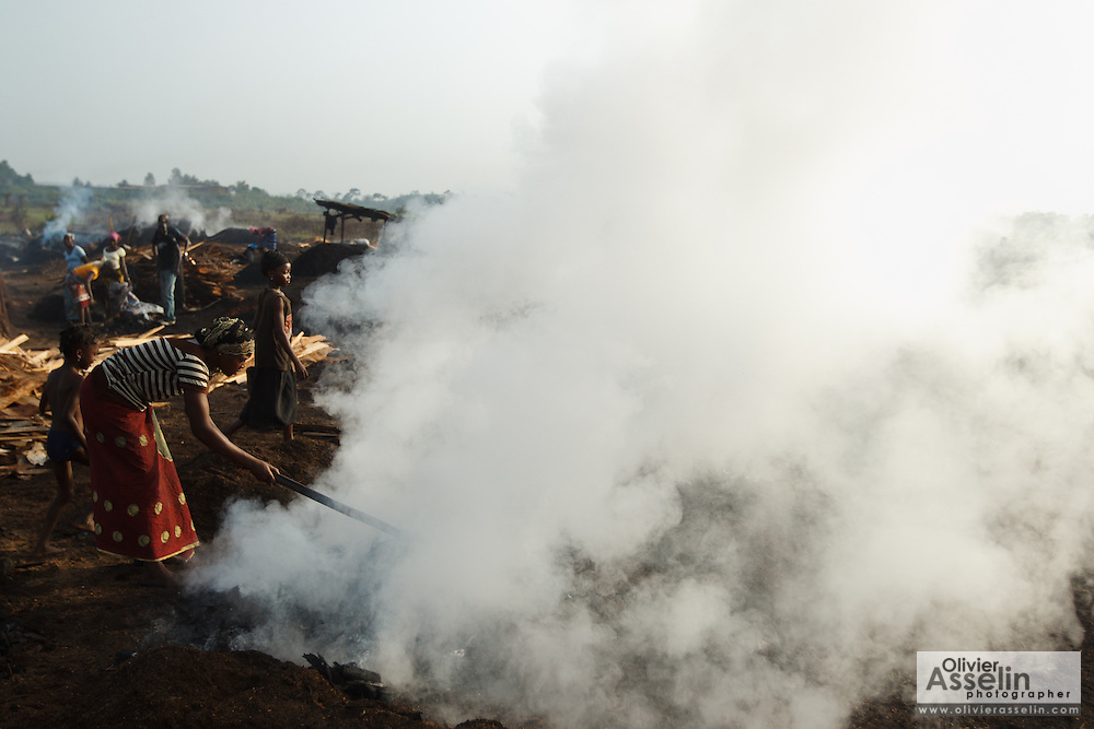 A woman uses a hoe to spread burning charcoal at a wood charcoal production site on the outskirts of San Pedro, Bas-Sassandra region, Côte d'Ivoire on Sunday March 4, 2012. Men, women and children - who don't go to school - work here seven days a week.
