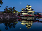 "As seen by the castle's red bridge, moonrise reflects in the moat of Matsumoto Castle, which was built 1592-1614 in Matsumoto, Nagano Prefecture, Japan. Matsumoto Castle is a ""hirajiro"" - a castle built on plains rather than on a hill or mountain, in Matsumoto. Matsumotojo's main castle keep and its smaller, second donjon were built from 1592 to 1614, well-fortified as peace was not yet fully achieved at the time. In 1635, when military threats had ceased, a third, barely defended turret and another for moon viewing were added to the castle. Interesting features of the castle include steep wooden stairs, openings to drop stones onto invaders, openings for archers, as well as an observation deck at the top, sixth floor of the main keep with views over the Matsumoto city."