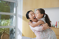 Smiling Woman Hugging her Daughter in living room