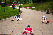 """30 JULY 2020 - DES MOINES, IOWA: People lay in front of the pedestrian gate to Governor's Mansion during a """"die in."""" About 45 high school students from across Des Moines marched from downtown to the Governor's Mansion to protest Iowa Governor Kim Reynolds' proclamation ordering Iowa schools to reopen to in person classes despite the COVID-19 pandemic. The students stood in front of the mansion and chanted before staging a """"die  in"""" in the street. The Governor's order mandates in person instruction rather than on line or a mix of on line and in person. Several school districts have indicated that they will disregard the Governor's orders and reopen with a hybrid system or mostly on line. The Governor will allow districts to apply for a waiver if the Coronavirus (SARS-CoV-2) infection rate is more than 15% in their community.     PHOTO BY JACK KURTZ"""