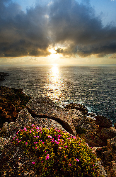Dramatic sunset across ocean from mountain Chapmans Peak South Africa