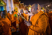 "25 FEBRUARY 2013 - BANGKOK, THAILAND:  Buddhist monks lead a candle light procession around Wat Benchamabophit Dusitvanaram (popularly known as either Wat Bencha or the Marble Temple) on Makha Bucha Day. Thais visit temples throughout the Kingdom on Makha Bucha Day to make merit and participate in candle light processions around the temples. Makha Bucha is a Buddhist holiday celebrated in Myanmar (Burma), Thailand, Cambodia and Laos on the full moon day of the third lunar month (February 25 in 2013). The third lunar month is known in Thai is Makha. Bucha is a Thai word meaning ""to venerate"" or ""to honor"". Makha Bucha Day is for the veneration of Buddha and his teachings on the full moon day of the third lunar month. Makha Bucha Day marks the day that 1,250 Arahata spontaneously came to see the Buddha. The Buddha in turn laid down the principles his teachings. In Thailand, this teaching has been dubbed the 'Heart of Buddhism'.     PHOTO BY JACK KURTZ"