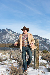 cowboy leaning on a fence near mountains