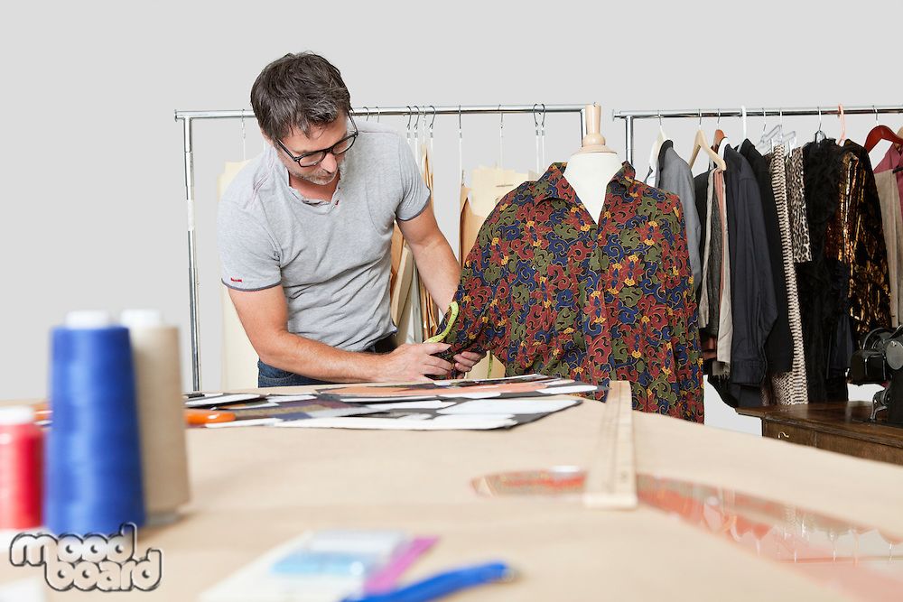 Mature male fashion designer taking measurement of shirt in design studio