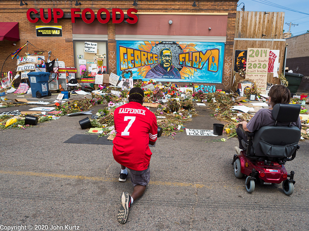 """12 JUNE 2020 - MINNEAPOLIS, MINNESOTA: A man wearing a Colin Kaepernick jersey at the impromptu memorial for George Floyd at the corner of 38th Street and Chicago Ave. in Minneapolis. The intersection is informally known as """"George Floyd Square"""" and is considered a """"police free zone."""" There are memorials to honor Black people killed by police and people providing free food at the intersection. Floyd, an unarmed Black man, was killed by Minneapolis police on May 25 when an officer kneeled on his neck for 8 minutes and 46 seconds. Floyd's death sparked weeks of ongoing protests and uprisings against police violence around the world.          PHOTO BY JACK KURTZ"""