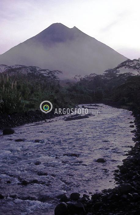 Cidade de La Fortuna. Parque Nacional Vulcao Arenal, a 90 km de San Jose na provincia de Alajuela.O vulcao tem uma altitude de 1.643 m e encontra-se dentro do Parque Nacional Vulcao Arenal com uma area de 10.800 ha. Em 1968 um forte terremoto fez ativar o vulcao e, desde esse dia que o vulcao estah em constante atividade e, quase diariamente, dao-se pequenas ou medias erupcoes. A noite se pode ver a lava borbulhante a correr pelas suas encostas. Na regiao a sua volta, predominan as nascentes de aguas quente e bosques tropicais. / City of La Fortuna, about 90 km north-west of San Jose, in the province of Alajuela. Vulcan Arenal National Park. The volcano has an elevation of 5,389 feet or 1,643 meters and encompasses the 26,690-acre or 10,800-hectare Volcan Arenal National Park. In 1968 a fateful earthquake awakened the slumbering giant. It has simmered ever since and barely a day goes by without a minor eruption. At nigh the red hot lava oozes down its steep slopes.Its environs offer soothing hot springs and fabulous hiking on the tropical forest.