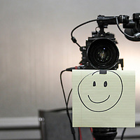 A drawing taped to a CBS camera encourages players to smile while doing their Q&A. ©Travis Bell Photography