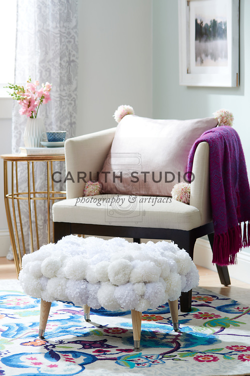 Pom-pom ottoman and pillow in living room