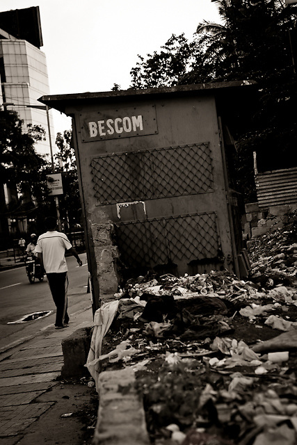 A picture of a sales hut on the side of the Old Airport Road in Bangalore, India. The road houses a lot of litter, as is snown in this photo.