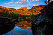 The moon sets at sunrise as Hallet Peak is reflected in Bear Lake, Rocky Mountain National Park, Colorado